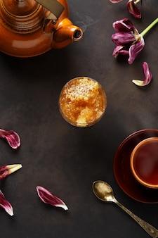 蜂蜜の背景。甘い蜂蜜の櫛とテーブルの上の熱い新鮮なお茶。
