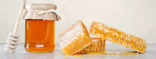 Honey background. sweet honey in the comb, glass jar.