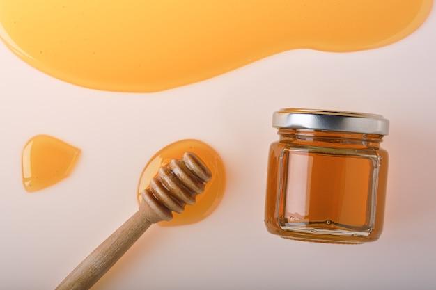 蜂蜜の背景。櫛の中の甘い蜂蜜、ガラスの瓶、テーブルの上に蜂蜜用のスプーン。明るい背景。上面図