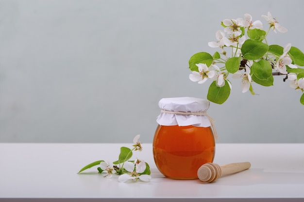 Медовый фон. сладкий мед в соте, стеклянной банке и ложке для меда на столе. светлый фон.