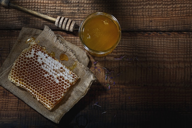 蜂蜜の背景。櫛の中の甘い蜂蜜、ガラスの瓶、テーブルの上に蜂蜜用のスプーン。上面図。