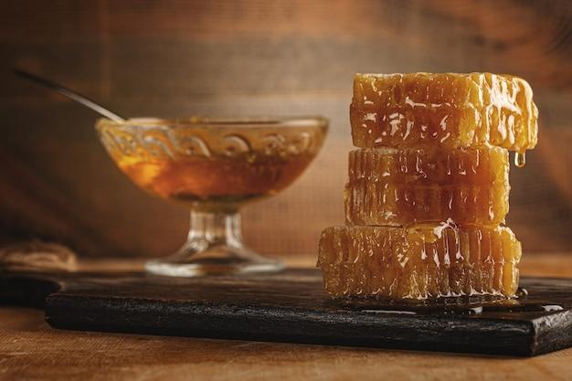Медовый фон. сладкий мед в соте, стеклянной банке и ложке для меда на столе