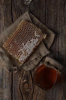 꿀 배경입니다. 빗 속의 달콤한 꿀, 유리병. 나무 배경에. 평면도.