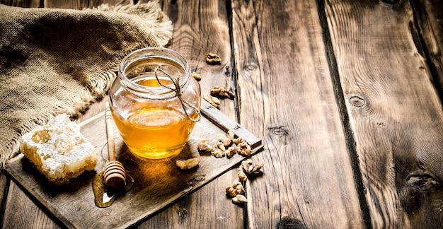 Медовый фон. сладкий мед в сотах, стеклянная банка с орехами. на деревянном фоне.