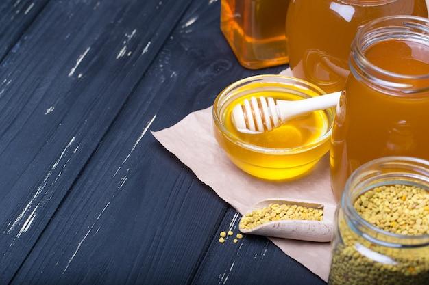 蜂蜜の背景。ガラスの瓶の中の甘い蜂蜜。木製の背景に。