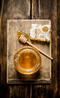 蜂蜜の背景。木の板に蜂蜜、蜂の巣、スプーンの瓶。木製の背景に。
