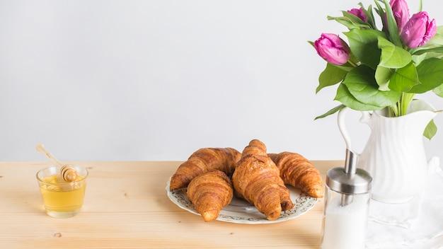 Miele; croissant al forno e vaso sullo scrittorio di legno contro fondo bianco