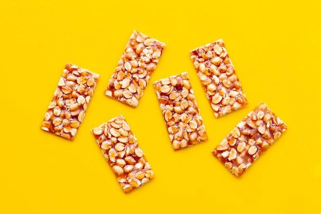 Медовые батончики с арахисом на желтой поверхности