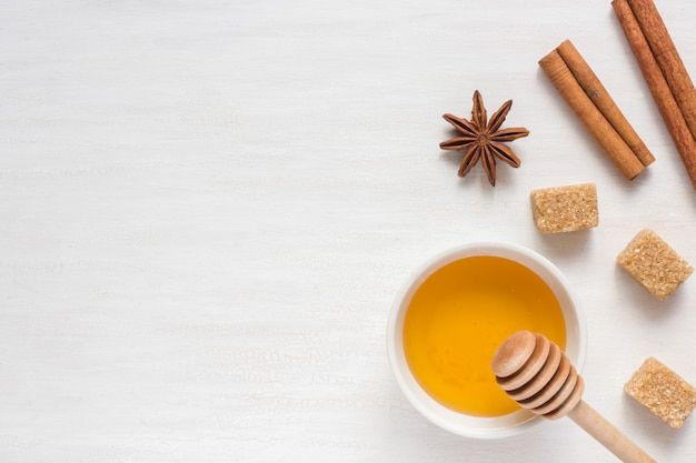 Honey, brown sugar and star anise with cinnamon on light background
