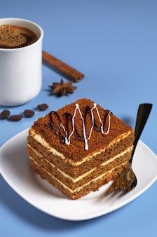 Медовый торт и чашка кофе на синем столе