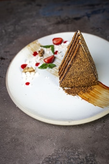 コンクリートの背景に白いプレート上の蜂蜜ケーキ