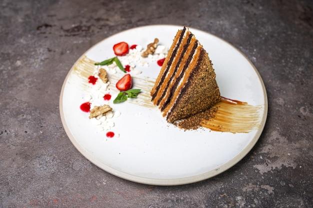 Медовый торт на белой тарелке на бетонном фоне