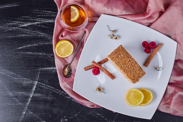 ティーカップの横にシナモン、レモン、ベリーと白いプレート上の蜂蜜ケーキ。