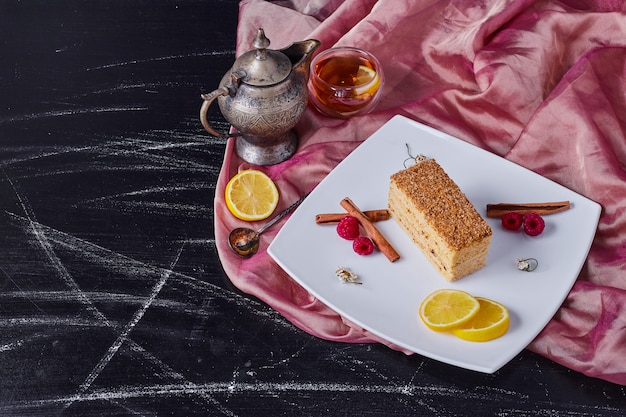 Honey cake with cinnamon and fruits on white plate next to tea.
