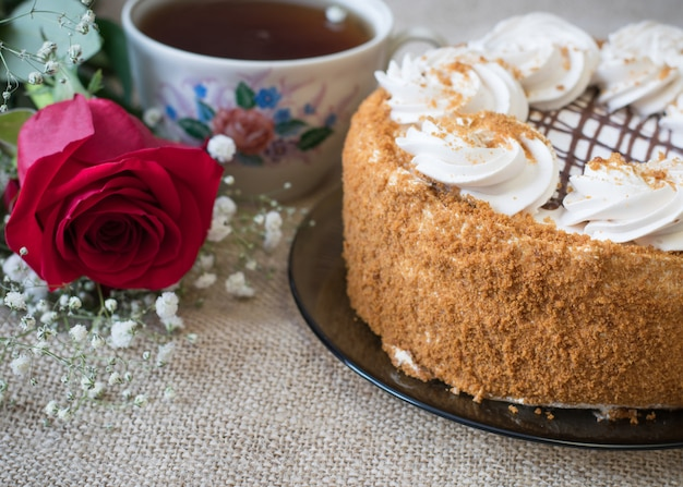 Honey cake with flowers and tea on the table
