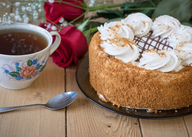 Honey cake with flowers and tea on a wooden table