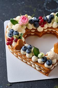 Медовик со свежей черникой, зеленью и сливочно-сырным кремом. десерт для любимого человека. сердечный торт. Premium Фотографии