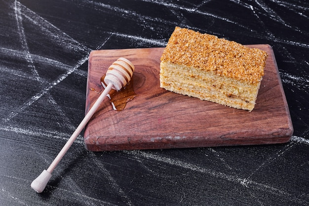 Torta di miele con cucchiaio di miele su sfondo scuro.