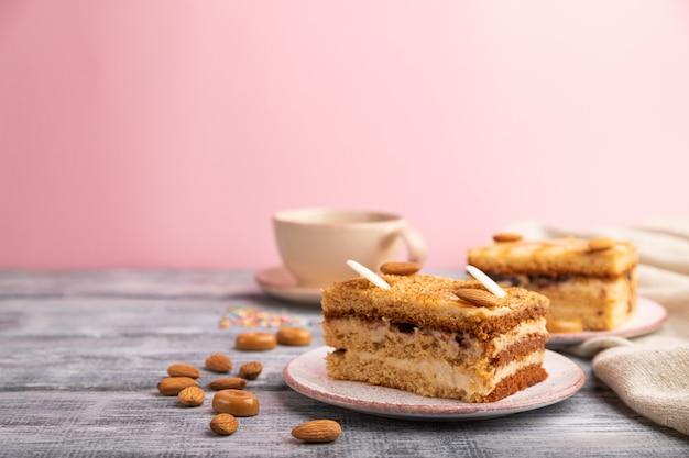 Медовик с молочным кремом, карамелью, миндалем и чашкой кофе на серо-розовом фоне