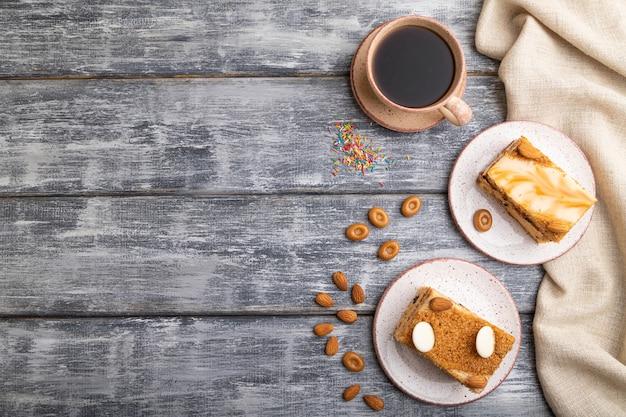 Медовый пирог с молочными сливками, карамелью, миндалем и чашкой кофе на сером деревянном фоне. вид сверху,