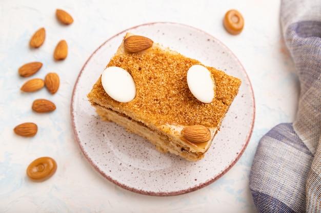 Медовый торт с молочными сливками, карамелью, миндалем и чашкой кофе на белом конкретном фоне. вид сбоку, выборочный фокус.