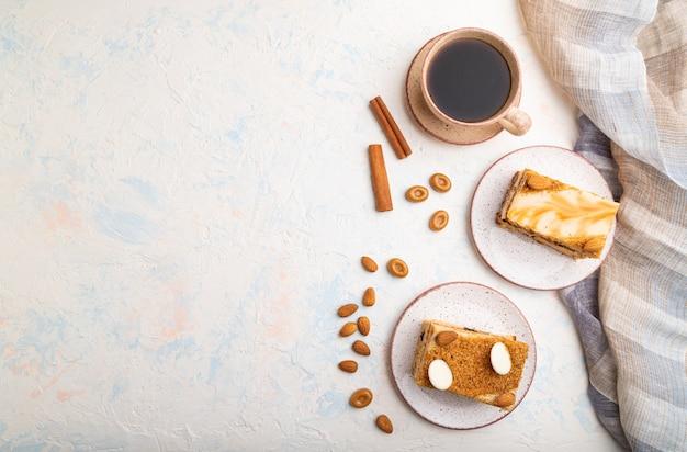 Медовый торт с молочными сливками, карамелью, миндалем и чашкой кофе на белом конкретном фоне. вид сверху,