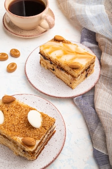 Honey cake with milk cream, caramel, almonds and a cup of coffee on a white concrete background and linen textile. side view, close up.