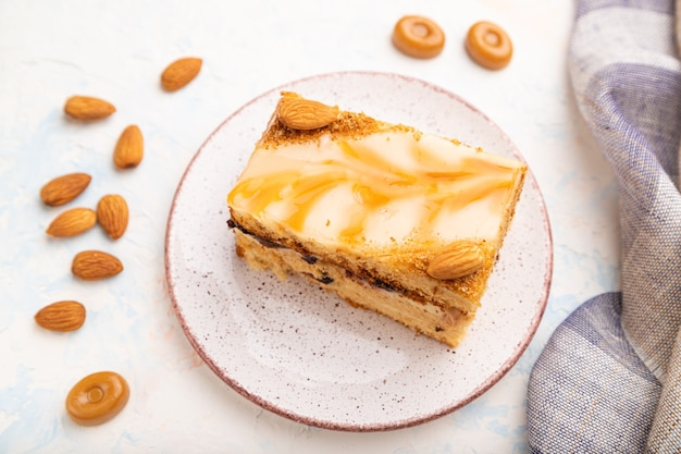 Honey cake with milk cream, caramel, almonds and a cup of coffee on a white concrete surface and linen textile