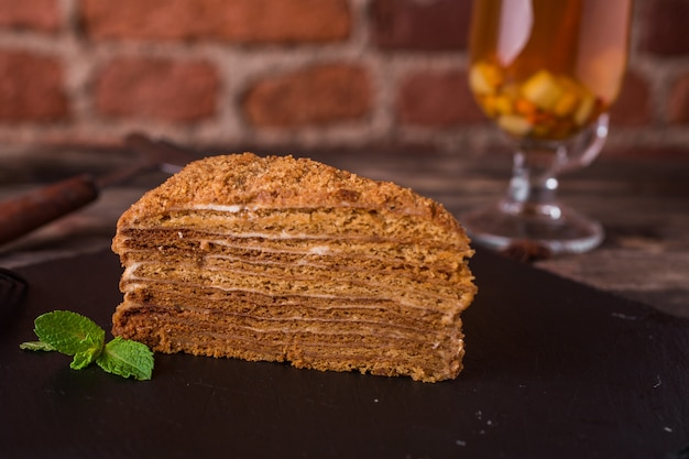 Honey cake with mint on a stone plate on rustic wood table