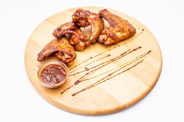 Куриные крылышки в меде с соусом барбекю на деревянной доске.