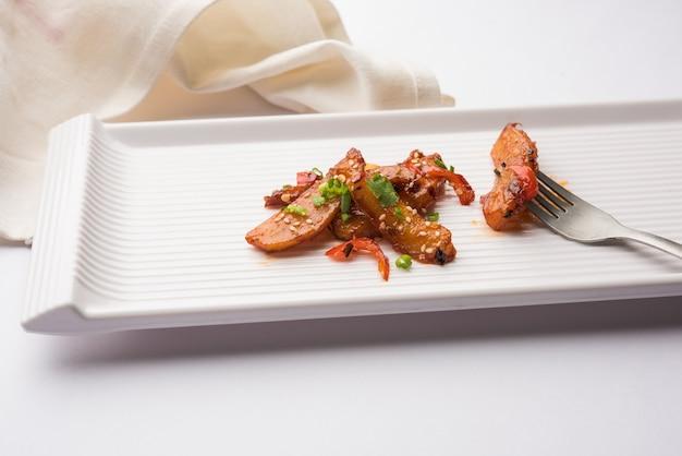 참깨와 양파로 장식된 인기 있는 인도-중국 스타터 레시피인 허니 칠리 포테이토 웨지. 선택적 초점