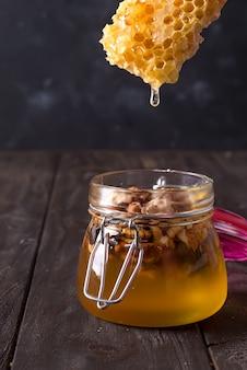Мед гребень капает из ковша в банку с орехами на старый деревянный стол.
