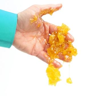 흰색 바탕에 인간의 손으로 떨어지는 꿀 빗. 건강한 신선한 음식