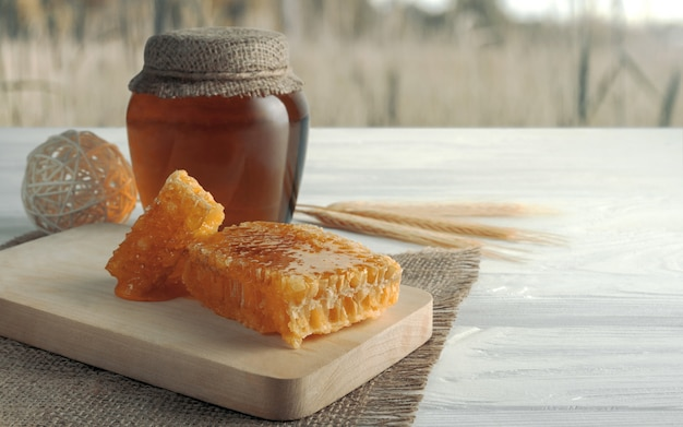 Honey comb and honey jar on table and wheat field in the background
