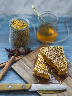 Honey comb pieces with spices; bee pollens jar and knife on backdrop