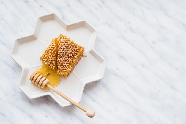 Honey comb pieces and wooden dipper in white plate against marble backdrop