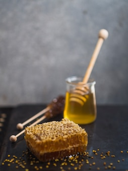 Honey comb with honey; wooden dipper and bee pollen