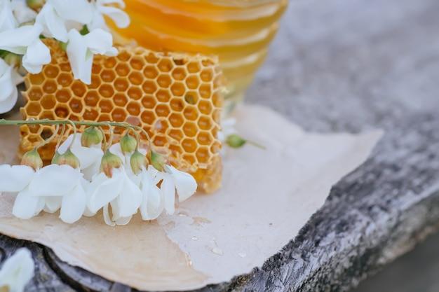 Медовые соты ломтик с ложкой и банкой. спаситель медового праздника концепции. скопируйте spase.
