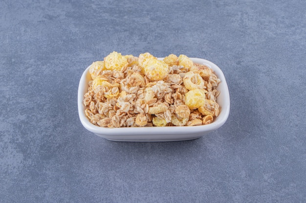 Anello di mais al miele con muesli in una ciotola, sullo sfondo di marmo. foto di alta qualità