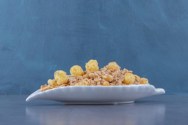 Anello di mais al miele con muesli in una ciotola, sullo sfondo di marmo.