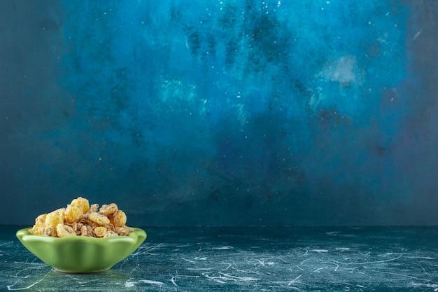 青い背景に、ボウルにミューズリーとハニーコーンリング。高品質の写真