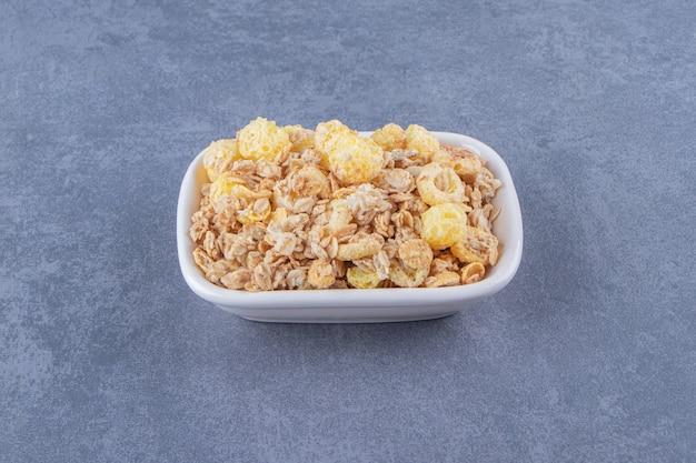 Кольцо из медовой кукурузы с мюсли в миске на мраморном фоне. фото высокого качества