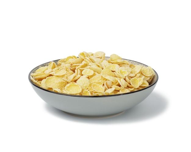 白い背景の上の蜂蜜コーンフレーク。ミルクと朝の朝食