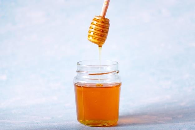 꿀 디퍼와 향기로운 꿀 떨어지는 그릇에