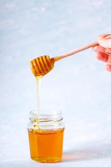 ボウルに落ちるハニーディッパーと香りのよいハチミツ