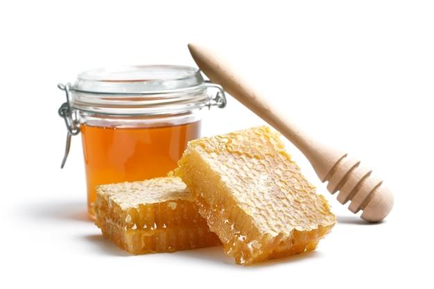 Ковш меда и мед в банке на белом фоне