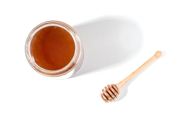 Ковш для меда и мед в банке на белой поверхности.