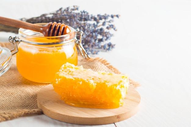 꿀 디퍼와 벌집. 꿀과 다양한 종류의 견과류와 견과류와 사과
