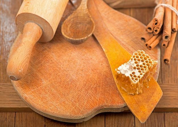 Медовый ковш и соты с лавандой, корицей и анисом на деревянной поверхности