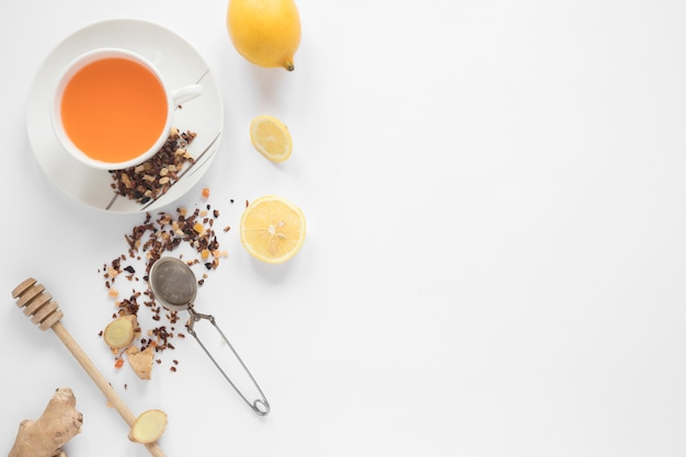 Honey dipper; strainer; herbs; lemon; ginger and cup of ginger tea on white backdrop